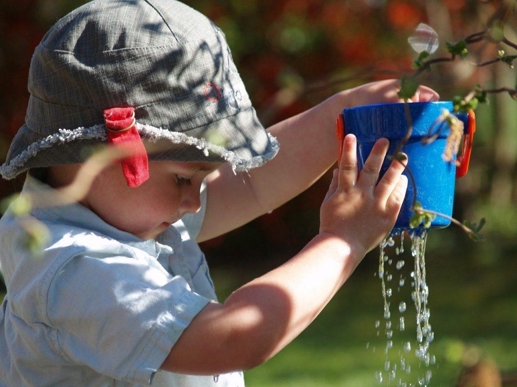 Kind Eimer Wasser undicht tropft